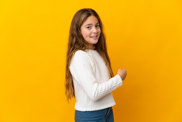 Niño sobre fondo amarillo aislado apuntando hacia atrás