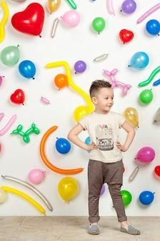 Niño sobre un fondo blanco con globos de colores niño en una camiseta sin mangas y pantalones
