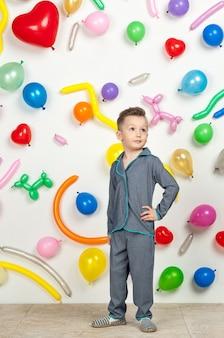 Niño sobre un fondo blanco con globos de colores niño en pijama sobre un fondo blanco con globos