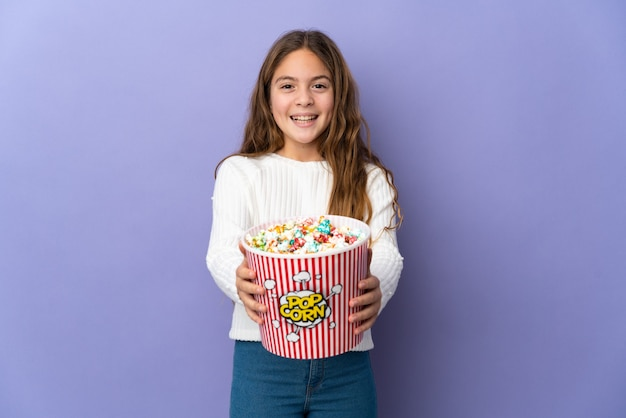 Niño sobre fondo púrpura aislado sosteniendo un gran balde de palomitas de maíz