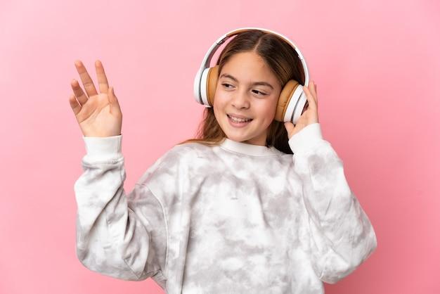 Niño sobre fondo rosa aislado escuchando música y bailando