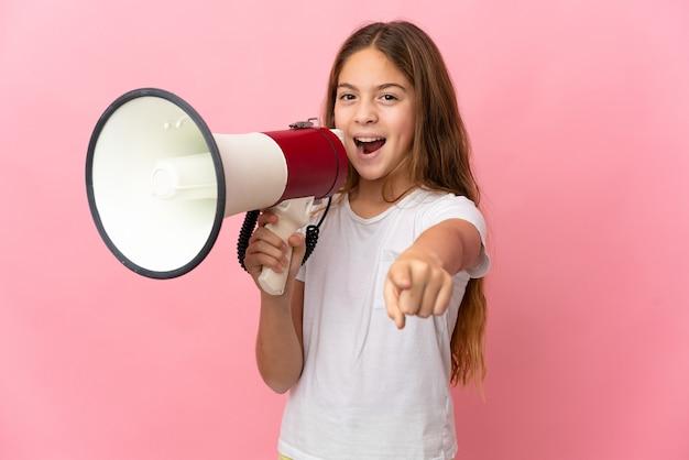 Niño sobre fondo rosa aislado gritando a través de un megáfono para anunciar algo mientras apunta hacia el frente