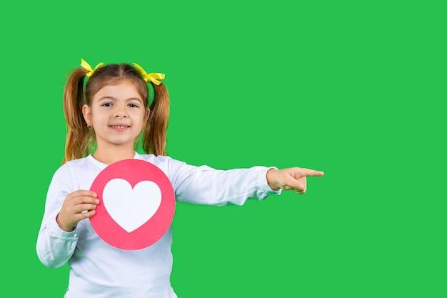 Un niño sobre un fondo verde aislado con un corazón muestra su dedo índice hacia un lado