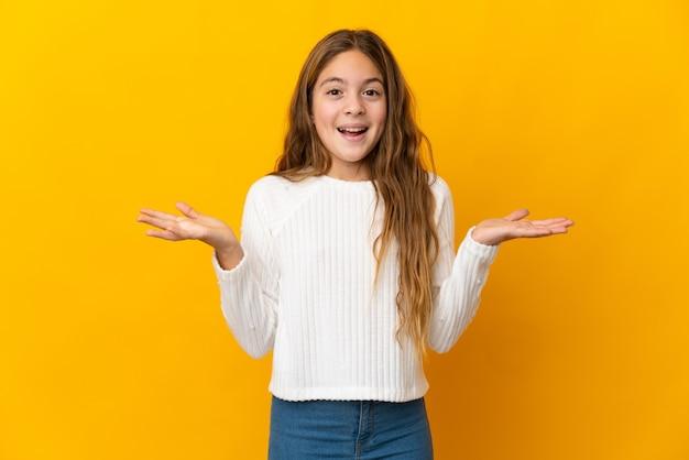 Niño sobre pared amarilla aislada con expresión facial conmocionada