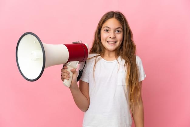 Niño sobre pared rosa aislada sosteniendo un megáfono y con expresión de sorpresa