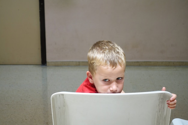 Niño solitario y huérfano espera asustado en la silla de una sala de espera.