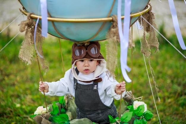 Un niño con sombrero de aviador se sienta en una canasta de un globo de juguete en un campo.
