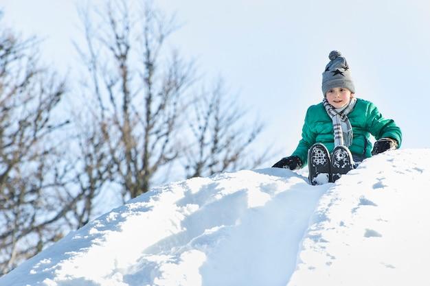 El niño con sombrero, bufanda y chaqueta verde se desliza hacia abajo desde un tobogán de nieve en la espalda.