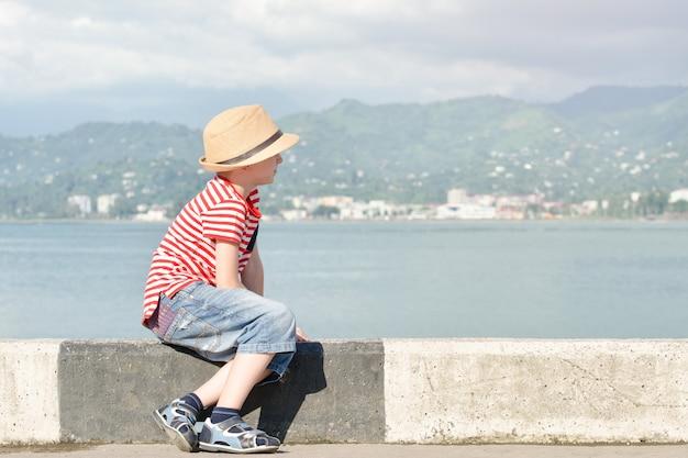 Niño con un sombrero y una camiseta a rayas sentado en la playa y mira al mar. vista lateral