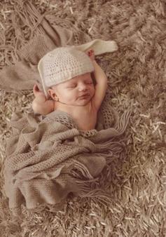Niño en sombrero como orejas de conejo duerme en la alfombra mullida