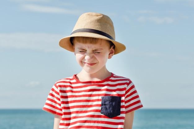 Niño con sombrero entrecerrando los ojos del sol. mar de fondo