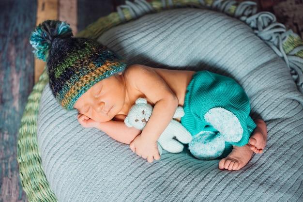 Niño con sombrero hecho punto duerme en almohada azul grande