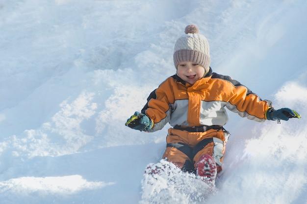 Niño con sombrero y mono naranja se desliza sobre el tobogán de nieve en la espalda