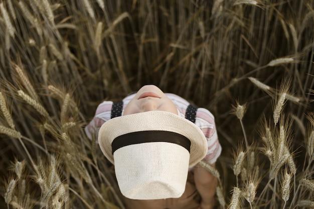 Niño con un sombrero de panamá mirando hacia arriba de pie en un campo de trigo