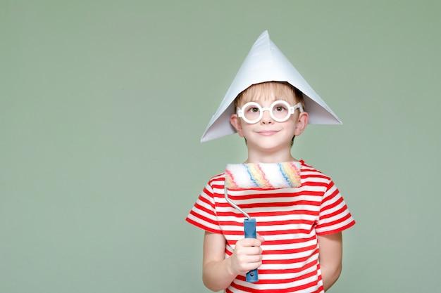 Niño con un sombrero de papel y gafas. retrato. rodillo para pintar
