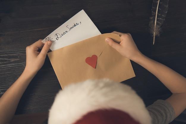 Niño en un sombrero de santa pone una carta para santa en un sobre. vista superior