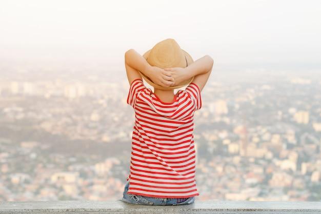 Niño con sombrero se sienta con las manos detrás de la cabeza y mira la ciudad