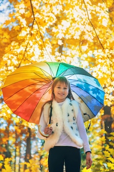 Niño bajo una sombrilla en el parque de otoño. enfoque selectivo.