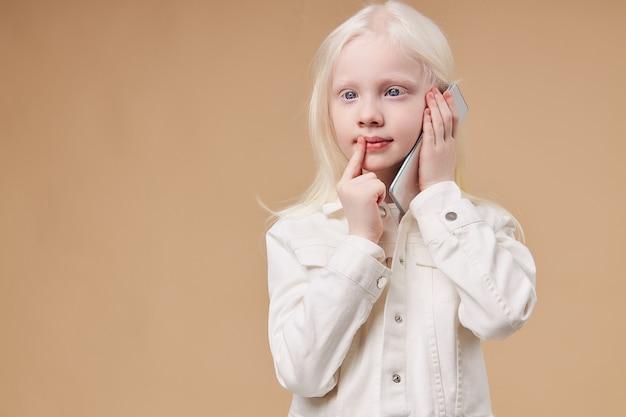 Niño soñador pensativo con síndrome de albinismo hablando por teléfono