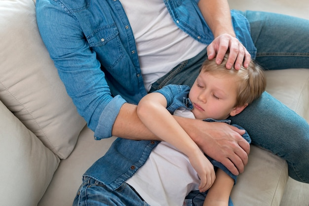 Niño soñoliento descansando su cabeza sobre las piernas del padre