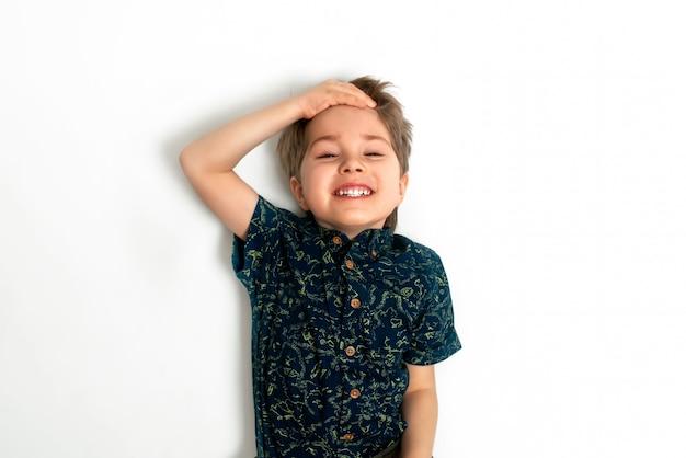 Niño sonríe y sostiene su cabeza. ríe y muestra dientes blancos