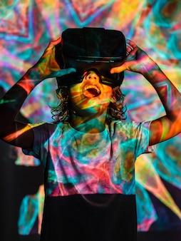 Niño sonriendo con gafas virtuales mirando una inyección de luces de colores