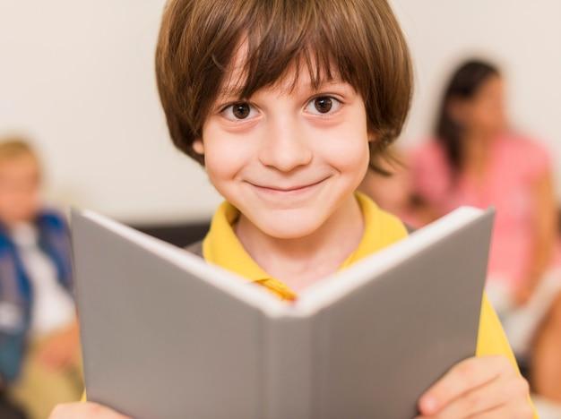 Niño sonriendo mientras sostiene un libro