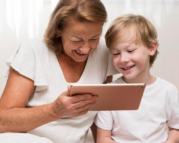 Niño sonriente y abuela con tableta