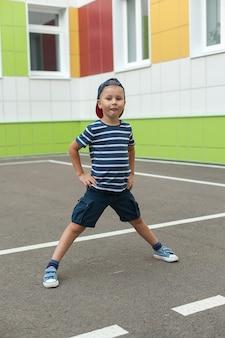 Niño sonriente alegre con gorra azul grande en la escuela