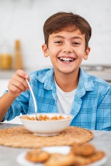 Niño sonriente de alto ángulo desayunando