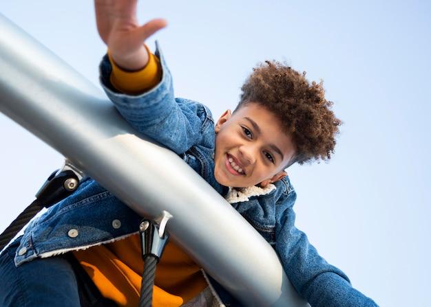 Niño sonriente de ángulo bajo divirtiéndose en el patio de recreo