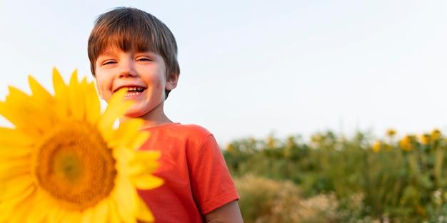Niño sonriente de ángulo bajo con girasol