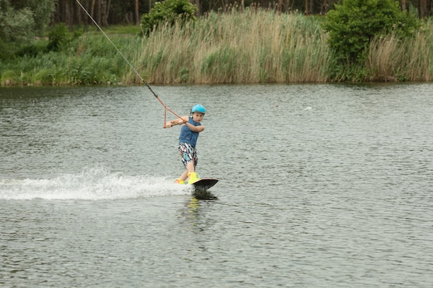 Niño sonriente aprendiendo a wake-board.