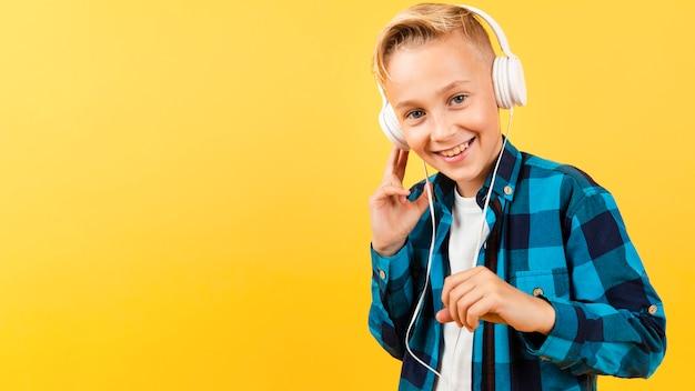 Niño sonriente con auriculares y espacio de copia