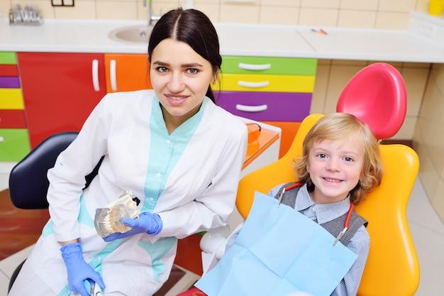 Niño sonriente con cabello rizado claro en el examen en el sillón dental
