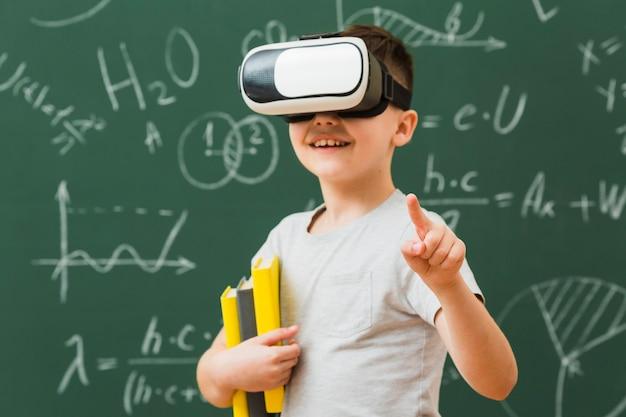 Niño sonriente con casco de realidad virtual y libros