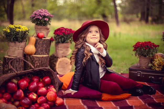 Niño sonriente con una cesta de manzanas rojas sentado en el parque otoño
