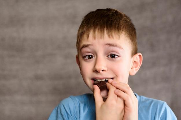 Niño sonriente comiendo un trozo de chocolate