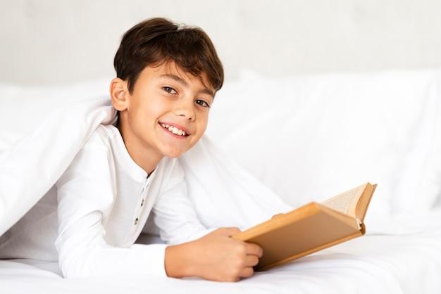 Niño sonriente cubierto con una manta mientras lee