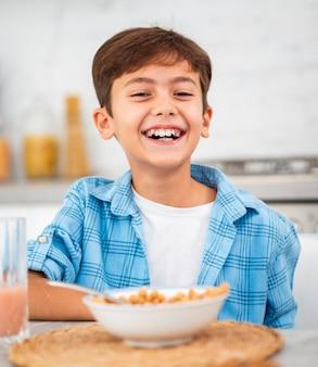 Niño sonriente desayunando en la mañana
