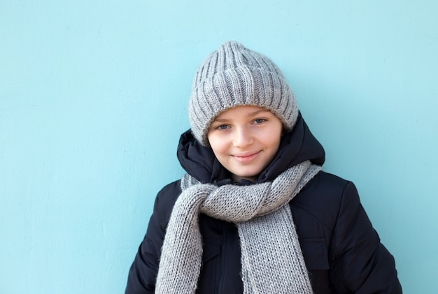 Niño sonriente divertido listo para vacaciones de invierno, niño de moda en invierno gorra gris y bufanda de pie contra la pared azul