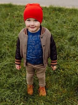 Niño sonriente feliz jugando al aire libre en un jardín.