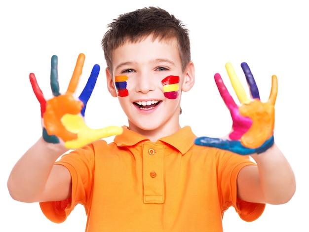 Niño sonriente feliz con las manos pintadas y la cara en camiseta naranja - en una pared blanca.