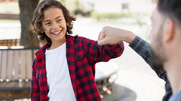 Niño sonriente golpeando el puño con su padre mientras está al aire libre