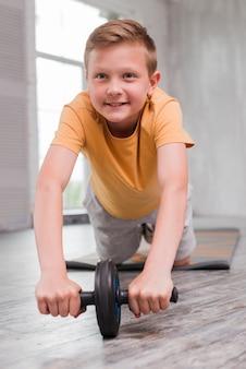 Niño sonriente haciendo ejercicio de lanzamiento de rueda ab en piso de madera dura