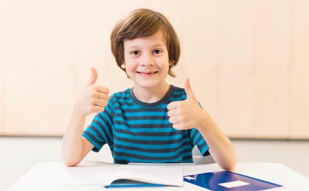 Niño sonriente haciendo el signo de los pulgares arriba
