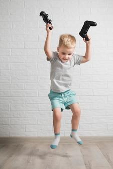 Niño sonriente con joysticks en mano saltando