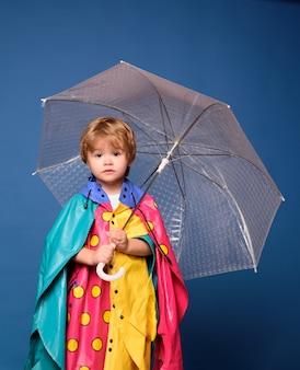 Niño sonriente jugando con hojas y mirando a cámara. muchacho alegre en impermeable con paraguas de colores.