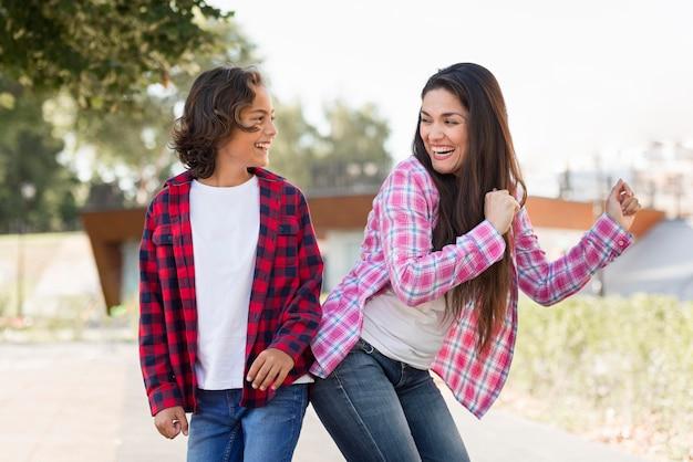 Niño sonriente y madre jugando juntos al aire libre