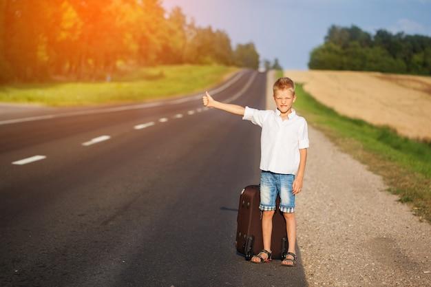 Niño sonriente con maleta viajando haciendo autostop. carretera de verano